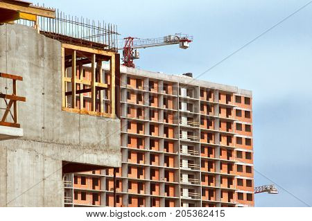 unfinished apartment house without windows and doors, building crane