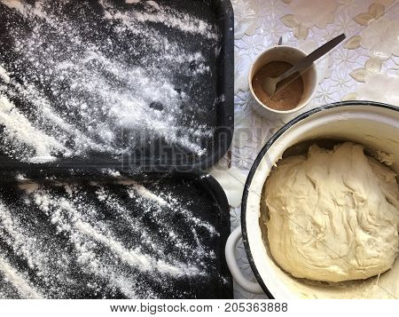 Preparation Of Buns With Cinnamon At Home. The Tray Is Sprinkled With Flour, Dough And A Wooden Roll