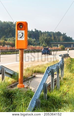 SOS phone. Emergency telephone at the roadside. Morning on the German highway