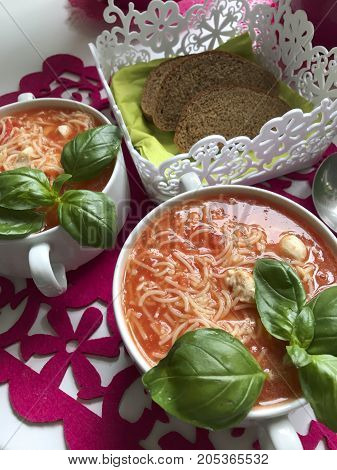 Tomato Soup, Decorated With Green Fresh Basil, It Is Worth On The Red Napkin With Bizarre Pattern. N