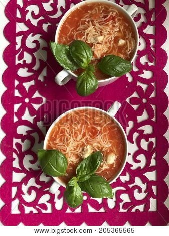Tomato Soup, Decorated With Green Fresh Basil, It Is Worth On The Red Napkin With Bizarre Pattern.
