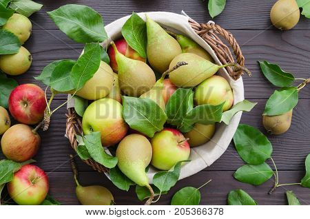 Basket with apples and pears on dark wooden background. Harvest concept. Top view flat lay overhead