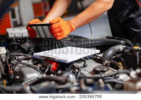 Specialist auto mechanic in the car service repairs the car. Replacement Air Filter