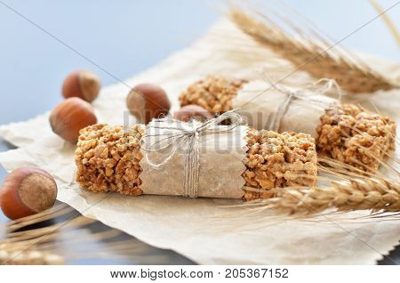 two muesli bars with filbert nuts and wheatear on backing parchment background