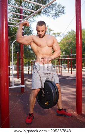 Healthy handsome and active man with fit muscular body, doing exercises. Sporty athletic male training outdoor.