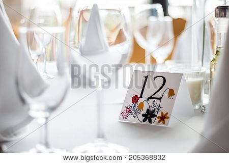 Number twelve at table for guests on wedding hall