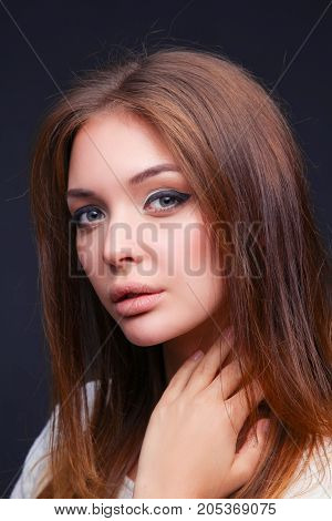 Beauty. Portrait of a young woman on dark background.