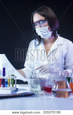 Medicine Concepts. Caucasian Female Laboratory Assistant Making a Mixture Using Glassware and Colorful Liquids in Lab. Vertical Image Orientation