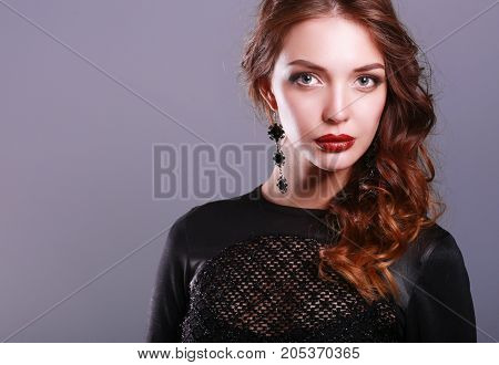 Beautiful woman with evening make-up in black dress.