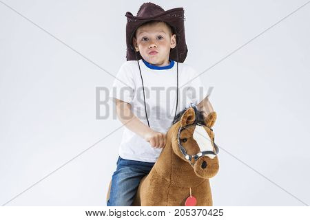 Kids Consepts. Portrait of Caucasian Little Boy in Cowboy Clothing Making Fases Posing With Symbolic Plush Horse Against White. Horizontal Image Composition