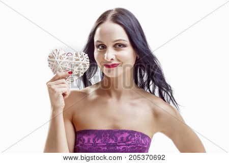 Smiling Caucasian Woman with White Wicker Heart Holding. In Front of Herself with One Hands. Horizontal Image Composition