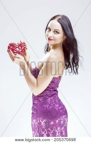 Emotions Concepts. Portrait of Caucasian Brunette Woman Demonstrating Red Wicker Heart as Symbol of Love.Vertical Image