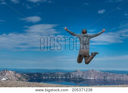 Man Leaps at Overlook to Crater Lake on Calm Morning
