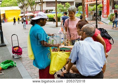 SINGAPORE - SEPTEMBER 7 2017: A fortune teller practices chiromancy by reading the palm of a devotee outside the Kwan Im Thong Hood Cho Temple on Waterloo Street in Bugis. The area is a famous haven for fortune tellers.