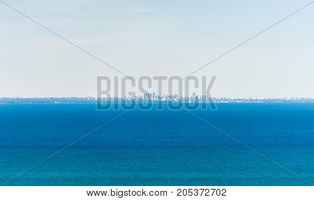 City of Mississauga Ontario Canada on distant horizon across expansive blue lake water under pale blue sky.