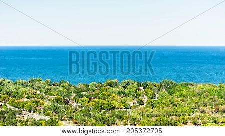 blue water between trees and houses on shore against white sky horizon at Lake Ontario Canada.