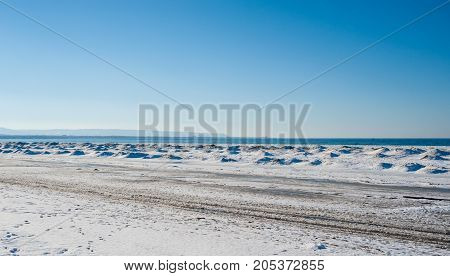 Frozen ice and sand dunes on beach in winter by lake under clear blue sky near Georgian Bay Ontario Canada.