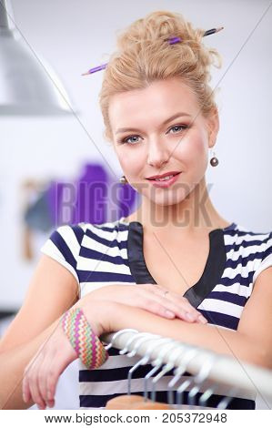 Beautiful young stylist woman near rack with hangers.