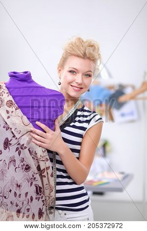 Fashion designer woman standing near mannequin in office