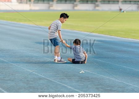 Boy Help Each Other On Blue Track After Fall