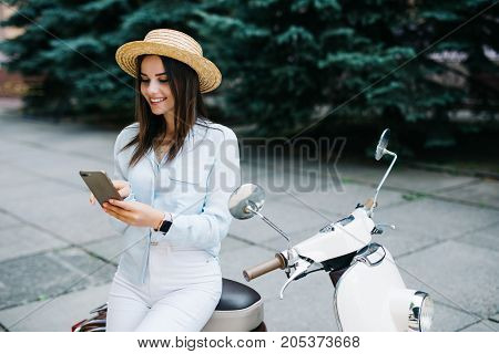 Young Woman Using A Smartphone While Standing By Her Motorbike