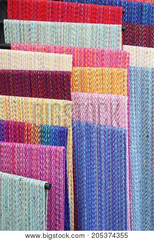Colorful handwoven textiles on a rack, vertical aspect