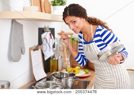 Woman making healthy food standing smiling in kitchen.
