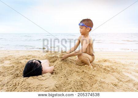 Boy Play With A Sand On The Beach
