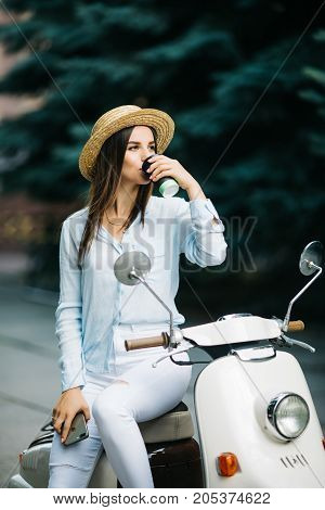 Happy Young Trendy Woman Drinking Takeaway Coffee Near Her Moped In The Morning