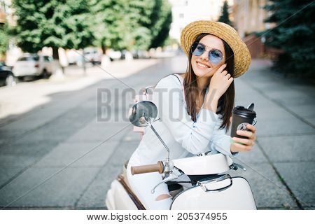 Young Woman Drinking Takeaway Coffee Near Her Moped In The Morning