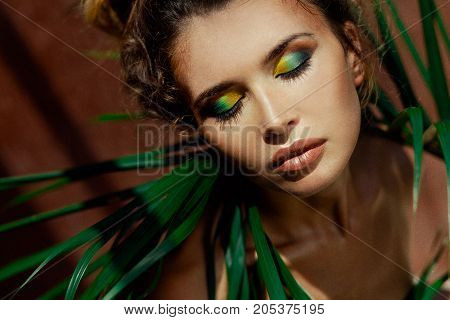 young beautiful woman with eyes closed on tropical background