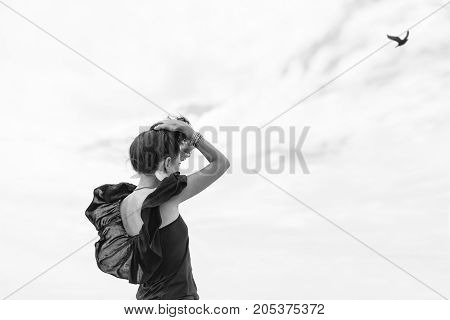 beautiful young woman in black dress outdoors looking at the bird in the sky