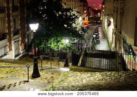 PARIS, FRANCE - 12th of OCTOBER 2012: Stairs, lights and historical buildings on Montmartre by night. October 12th, 2012. Paris, France.