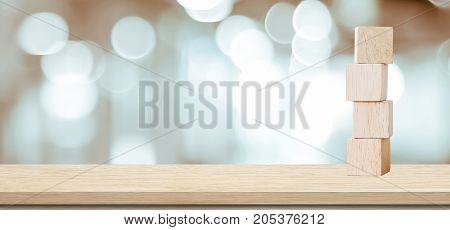 Four wooden cubes on table over blur abstract bokeh light background banner with copy space for text