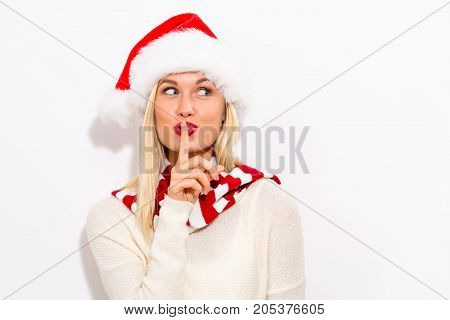 Young woman with Santa hat making a quiet gesture