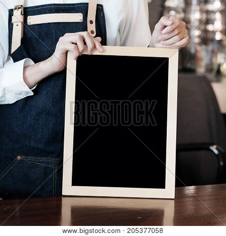 Women Barista holding blank chalkboard at cafe counter background menu background food and drink industry concept