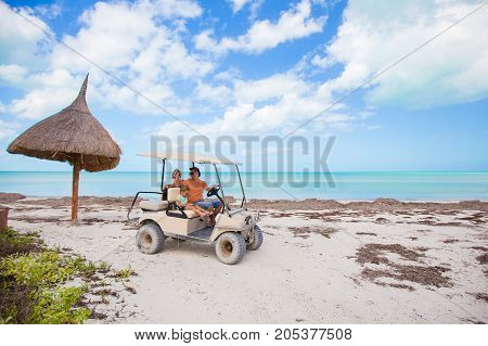 Dad and little daughter driving golf cart on tropical beach