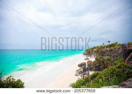 Stunning cliff side views of Tulum ruins by the Caribbean Sea in Mexico on sunny day