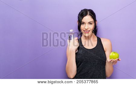 Happy young woman holding an apple and a water bottle