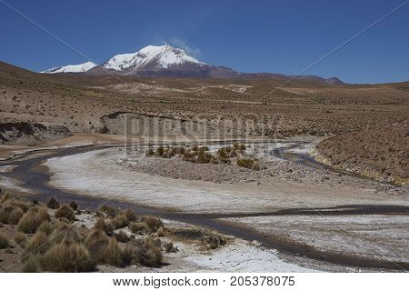 Meandering path of the River Chuba on the Altiplano of northern Chile in Lauca National Park. Snow capped peak of Volcano Guallatiri in the distance.