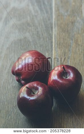 Three red apples on a wood table.