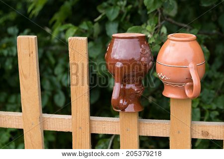clay jugs on a wooden fence. horizontal day shot close-up