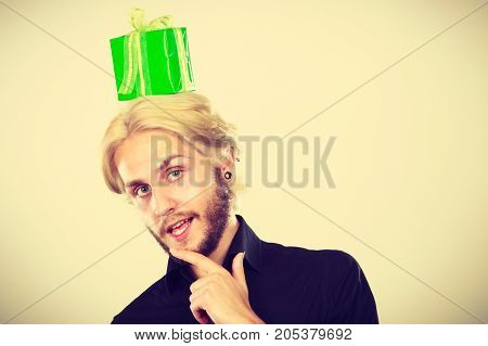 Celebration and giving concept. Cool young man with green gift box on his head. Guy thinking looking for present idea
