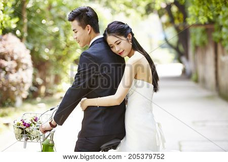 newly-wed asian bride and groom riding a bicycle.