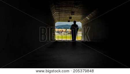 The silhouette of a football fan enters the under pass upon returning from a local youth football game.