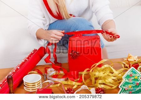 Holiday gifts seasonal concept. Woman in sitting on sofa preparing and packing christmas presents