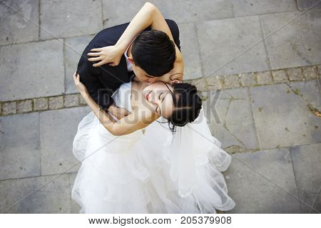 young asian bride and groom embracing kissing dancing high angle view.
