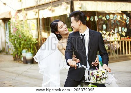 romantic asian newly wed couple having fun riding a bicycle together.