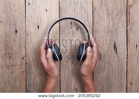 hand hold headphone on wooden plank background