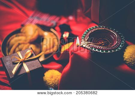 stock photo showing Diwali still life with Diya or oil Lamp, gift boxes, sweets and fire crackers with flowers arranged over red satin cloth with bokeh